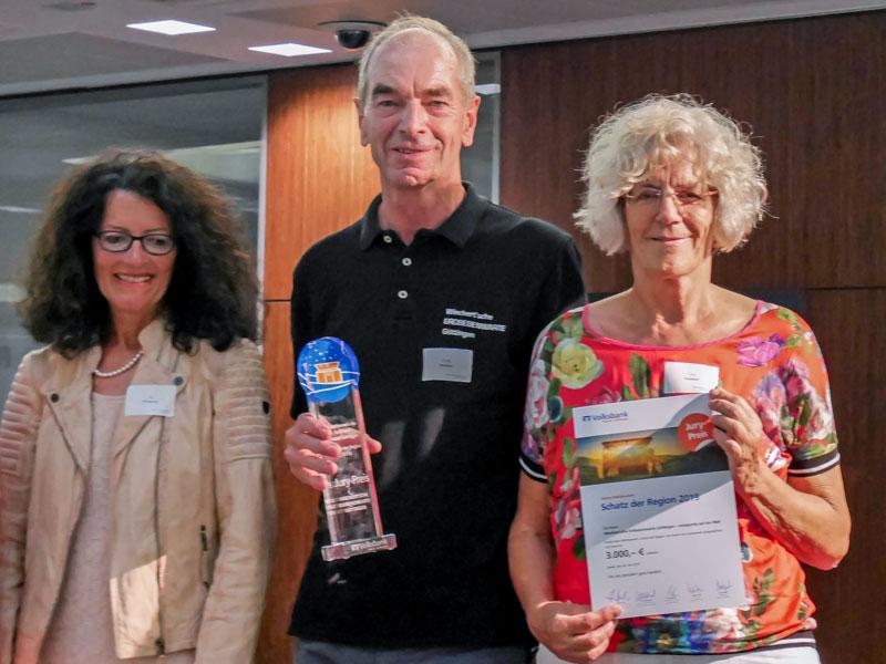 """Die Vereinsmitglieder Petra und Udo Wedeken mit Urkunde und """"Pokal"""" auf der Bühne"""